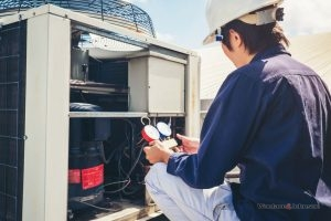 An HVAC professional ways his options for emergency air conditioner repair services.