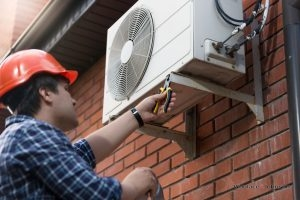 Technician performs air conditioner repair on an outdoor unit.
