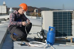 HVAC technician conducts emergency air conditioner repairs
