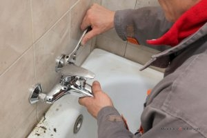 Plumber conducts faucet repair