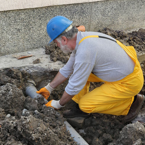 Worker Finishing Sewer Line Repair