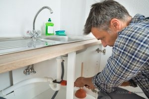 A plumber conducts kitchen and bathroom repairs on a sink.