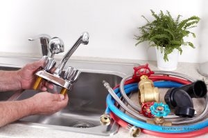Plumber removes broken faucet to conduct faucet repairs.