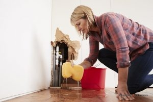 A woman attempts to clean up before emergency plumbing repairs.