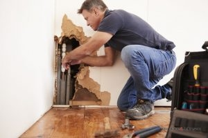 A plumber performs one of his many plumbing services on a pipe inside of a damaged wall.